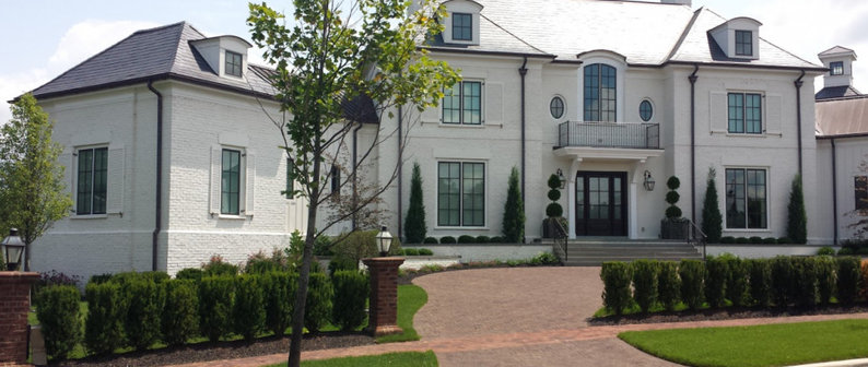 A sprawling colonial revival home lined by trees.