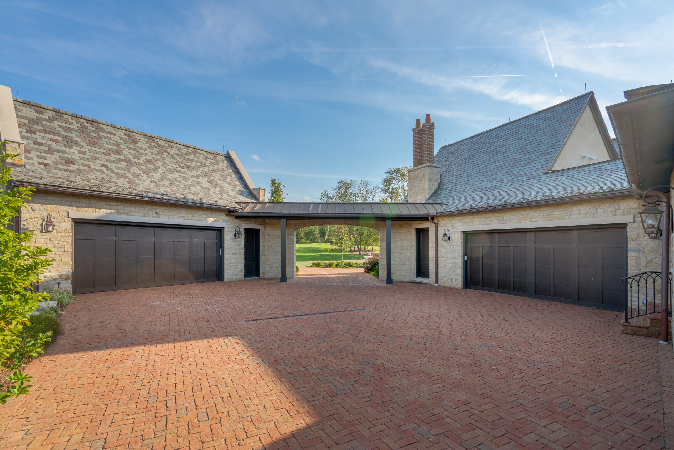 A brick driveway with two garages on either side of an entryway.